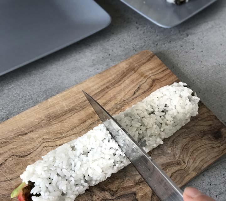 Die Messerklinge befeuchten, dann klebt der Reis beim schneiden der Rollen nicht so schnell an der Klinge.