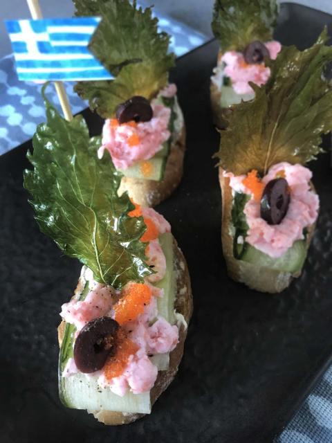 Eine kleine Vorspeisenplatte aus Brotscheiben mit Gurkenstreifen, Taramosalata, Oliven und Shisoblättern.