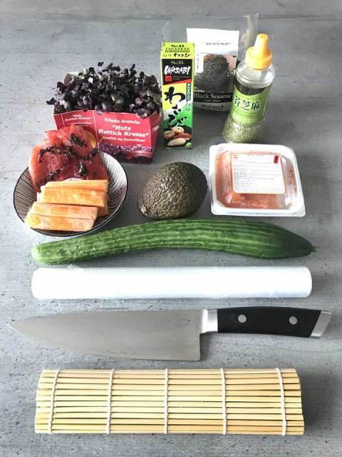 Die Zutaten für die California-Maki in der Übersicht: Rettichkresse, Lachs, Surimi, Avocado, Gurke, Tobibiko, Wasabi und Sesamkörner.
