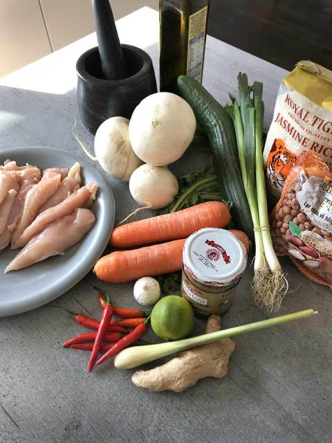 Die Zutaten für die Hühnchen-Saté-Spieße: Hühnchenfilets, Karotten, Tamarinden-Sauce, Knoblauch, Limetten, Zitronengras, Chilie, Frühlingszwiebeln, Reis und Erdnüsse.