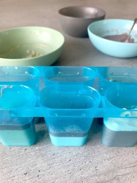 Die Schichten vorsichtig mit einem kleinen Löffel in die Formen füllen. Besonders hübsch sieht das Eis aus, wenn die Schichten in unterschiedlichen Mengen und Reihenfolgen in die Formen gefüllt werden.