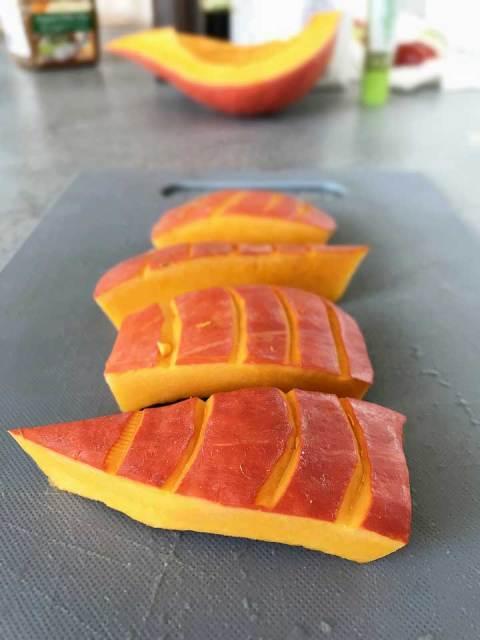 Die Kürbisspalten halbmondförmig mit einem Messer einschneiden.