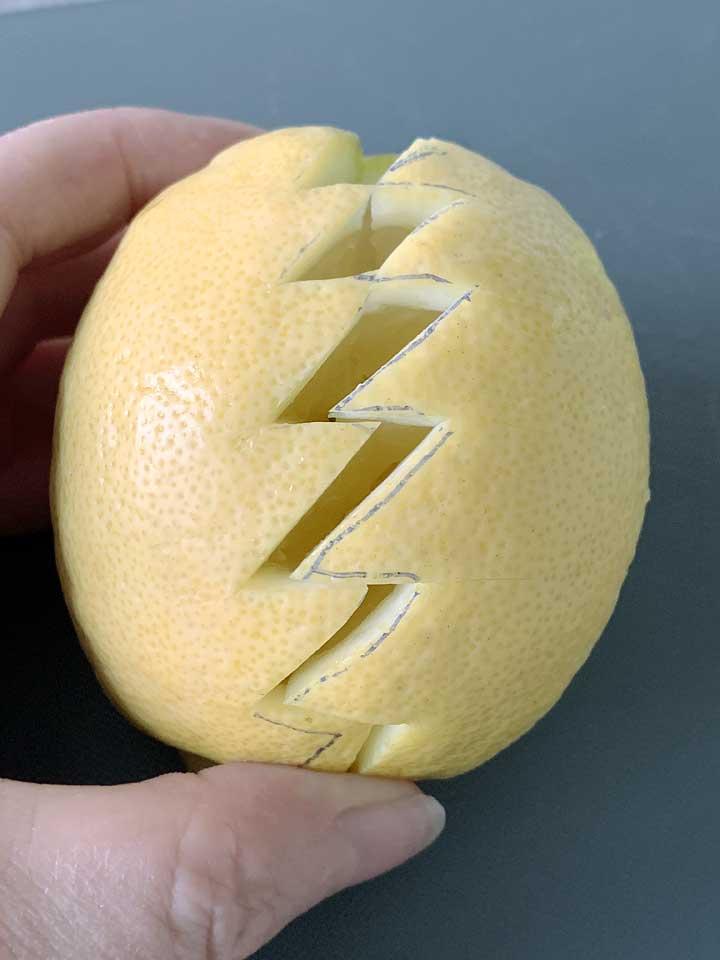 Die Zitronen mit einem spitzen Messer zickzackförmig einschneiden.