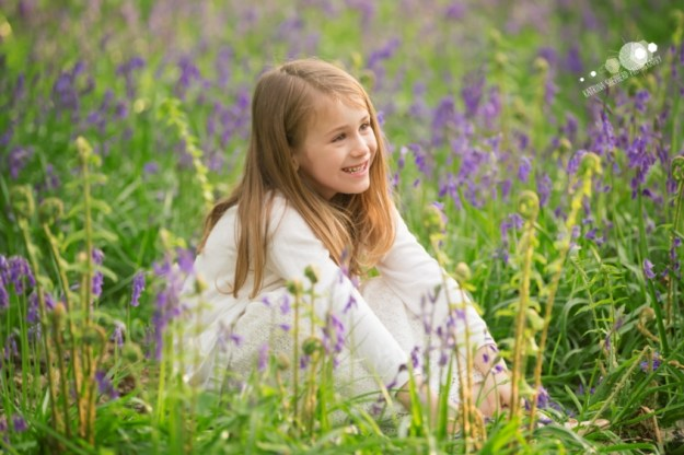 A girl sitting in amongst the bluebells looking off to the right - Spring Wood near Whalley