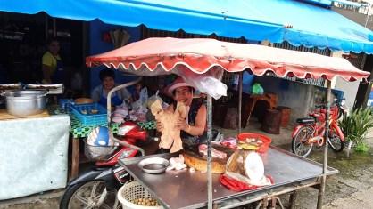 Fröhliche Marktfrau in Ranong, die Schweinespezialitäten verkauft
