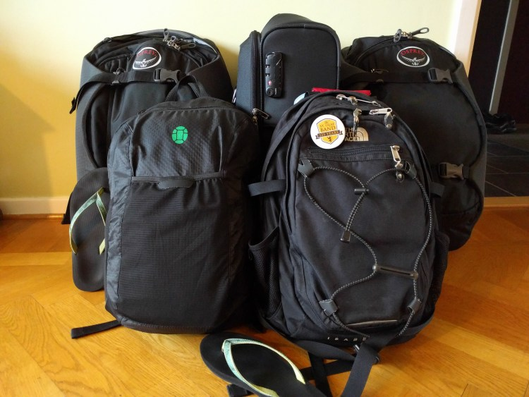 four backpacks and one small suitcase