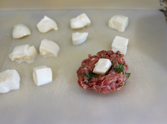 Add the mozzarella piece to the inside of the meatball