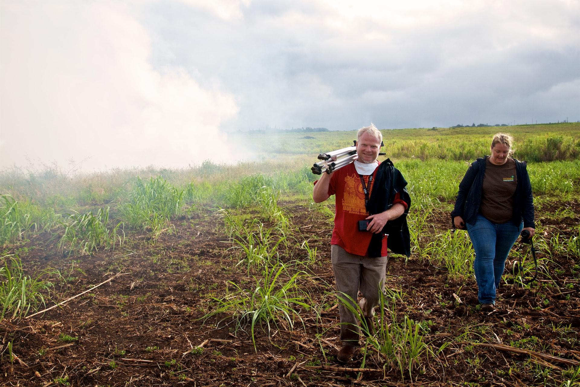 Director Danny Miller and Hilary Bingman of Hawaiian Commercial & Sugar Company on Maui at a sugar cane burn before a harvest. Photo by Baron Sekiya