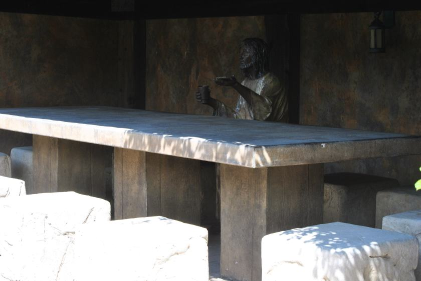 Jesus seated at a table with stone stools surrounding it for seating.