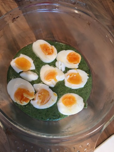 Halved boiled eggs in the spinach sauce