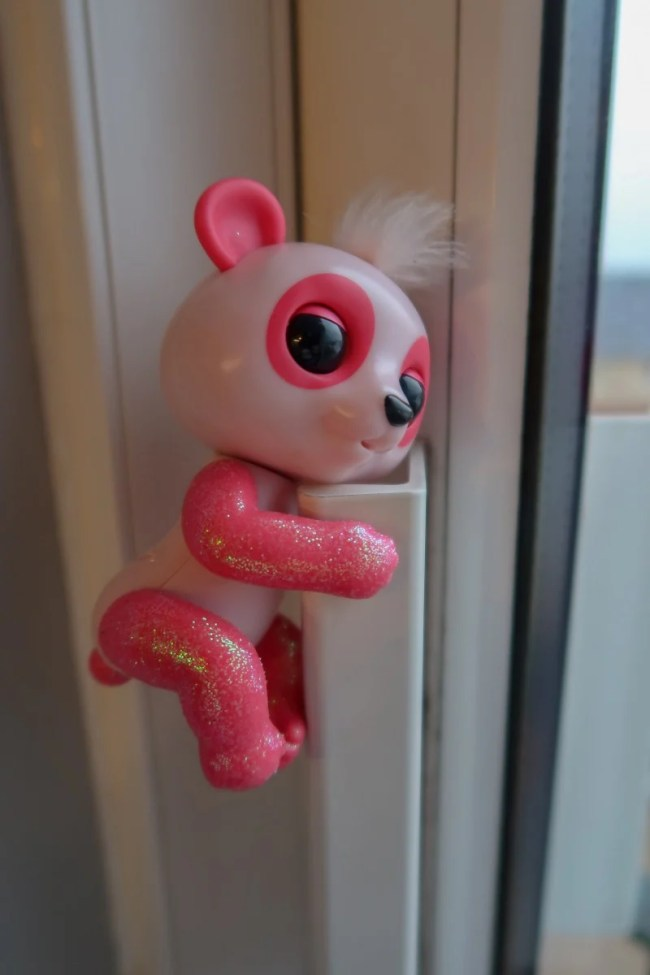Pink Baby Panda Polly Fingerling hanging out on the door
