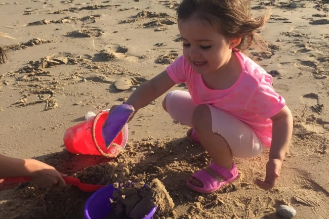 Daisy playing with a bucket and spade on the beach.
