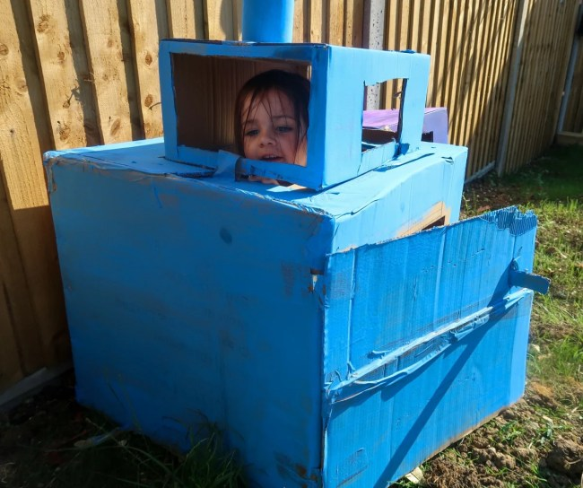 Daisy inside a blue painted cardboard train with a door and handle