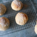 Soft white rolls on a cooling rack with a grey backdrop