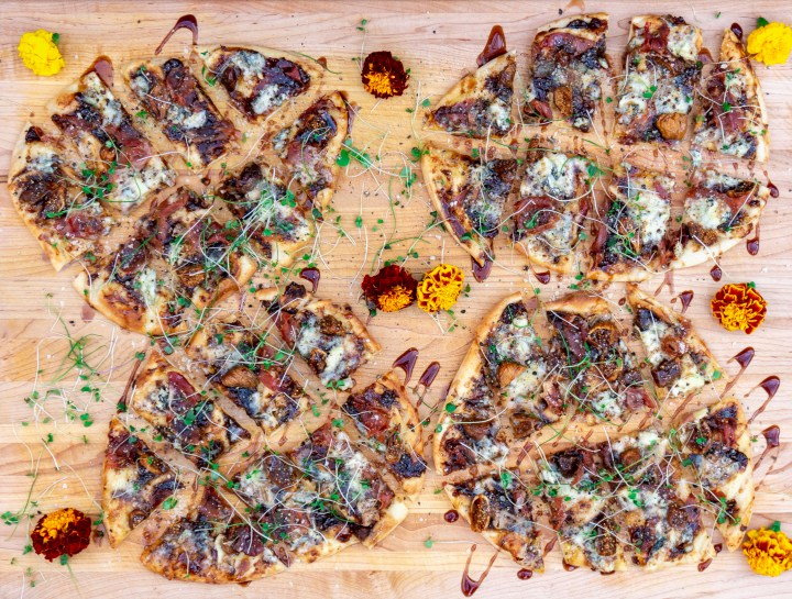 large board with 4 fig flatbreads and all toppings