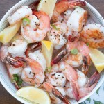 overhead shot of roasted shrimp with lemon wedges