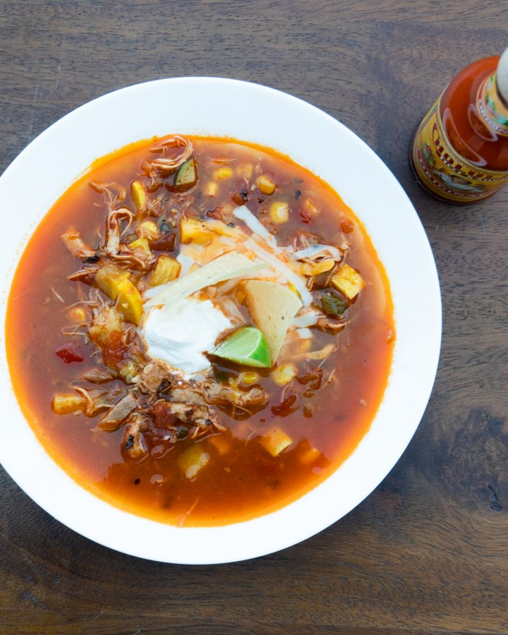 bowl of chicken tortilla soup with toppings and cholula sauce