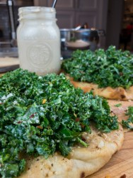 Lemon Tahini Kale Flatbread with dressing container behind