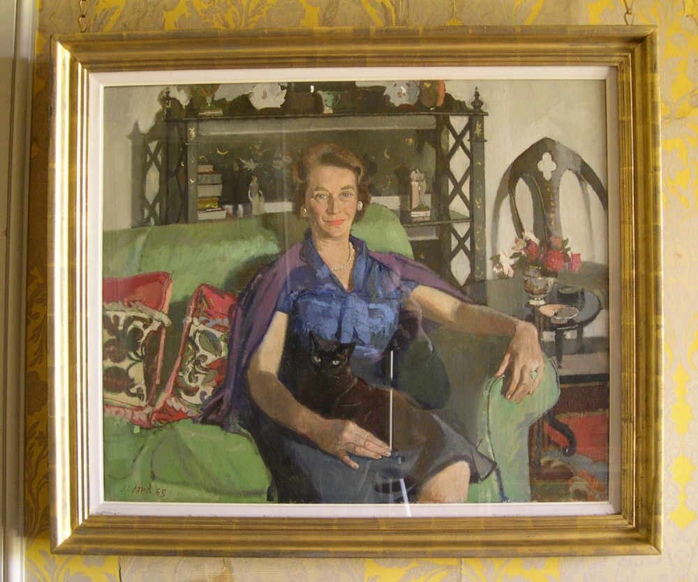 Oil painting on canvas, Elizabeth (Betty) Kerr-Smiley, Mrs Christopher Hussey (1907-2006) in Middle Age by John Ward, RA (Hereford 1917 - 2007), signed in brown at the bottom left: J Ward '65' [1965]. A three-quarter length portrait, seated slightly to right, looking out, gazing at the spectator, in a green sofa with two embroidered cushions, and with japanned etagere behind her, a black cat in her lap, looking out; wearing blue dress, plum-coloured cardigan over her shoulders, and single-row pearl necklace. Mid brown hair, and green eyes.