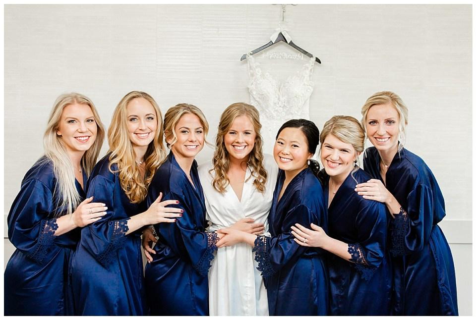 Bridesmaids getting ready in silk navy robes at Mendakota Country Club in Eagan, MN