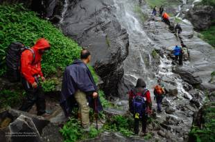 Hampta Pass Trek- passing under a waterfall