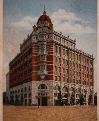 【6】辰野金吾が手掛けた日本初のテナントビル。今はなき、京橋のシンボル第一生命本館(第一相互館)。日本最初のテナントビル。第一生命保険は、1902年(明治35年)に日本初の相互会社として設立された。中央通りと鍛冶橋通りの交差点の南側の土地は、当時南伝馬町3丁目の地名で商家が立ち並ぶ一角であった。創業者の矢野恒太は、日本銀行本店や東京駅を設計した辰野金吾に相談を持ちかけた。鉄骨煉瓦造7階建で、5・6階に第一生命の事務所が入り、2~4階は貸事務所、1階は貸店舗とされた。自社は上層階に入り手狭になったら順次下の階に事務所を広げる狙いがあった。第一次世界大戦による建築材料不足のため工期は大幅に遅れた。国内で鉄骨を賄うことができず英国ドルマン・ロング社に発注したが、鉄骨を積んだ八阪丸がドイツの潜水艦の攻撃を受け地中海に沈むトラブルもあった。完成を見ることなく辰野金吾がスペイン風邪で急逝。関東大震災で倒壊せず戦中戦後、京橋の景観を作ってきた。惜しまれつつも1969年(昭和44年)解体。2011年(平成23年)完成した3代目、相互館110タワーでも塔の意匠は継承されている。【6】1921年(大正10年)・第一生命保險相互會社