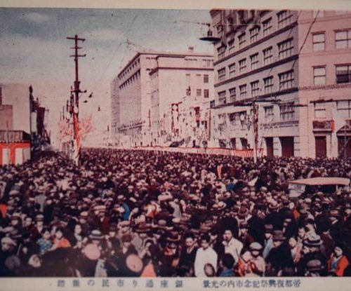 【14】帝都復興祭。関東大震災後、政府は帝都復興院を設け首都の再建に取り組む。復興事業の大部分が終え、昭和5年(1930年)3月24日より1週間にかけ「帝都復興祭」が盛大に開催された。初日は天皇陛下の市内巡幸でスタート。宮城を出発後は神田、浅草を経由し、隅田川の言問橋から蔵前橋など復興された橋梁を渡る32キロ程という、異例の長巡行に、各沿道は百万人もの人々で埋め尽くされた。復興資金は、第一次大戦で日本軍の活躍を見ていたアメリカ、イギリス、中華民国からは溥儀から膨大な支援金が贈られた。こうした内外の協力の末、無事復興が終わったため、昭和天皇ご臨席の式典、ダンスパーティーや演奏会、映画上映など文化的なもの、スポーツ大会も行われ、帝都復活を国内外に示すこととなった。【14】1930年(昭和5年)・(帝都復興式典祭記念市内の光景)銀座通り市民の雑踏