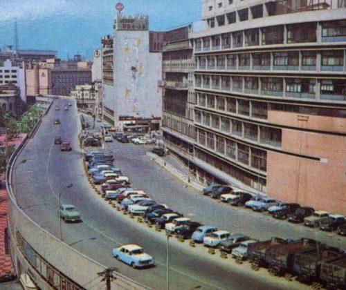 【36】日本初の高速道路。モータリゼーションの時代。1964年(昭和39年)東京オリンピック開催に向け、戦後の東京大改造の一環として、新橋から京橋までの旧江戸城外堀が埋め立てられ、その上に東京高速道路が建設された。日本で唯一の民間による、店舗ビルの屋上を道路が走る高速道路ビル。1962年(昭和37年)開通した首都高速よりも歴史が古く、部分開通は1959年(昭和34年)に遡り、1966年(昭和41年)全線開通。夜は銀座のまばゆいばかりの光が見えて美しいが、中央分離帯がない対面走行となり注意が必要な道路である。一般自動車道と異なり区間内のみであれば無料で通行可能。これは東京都が建設を許可する際に、公共河川を利用することから無料化を条件としたためである。高架下地下1階から地上2階に「有楽フードセンター」が誕生。当時としては、駅ビルもない時代。食に関する総合デパートといえる規模で注目された。都庁移転問題を契機に1989年(平成元年)名称を「銀座インズ」し全面リニューアルされた。【36】1963年(昭和38年)