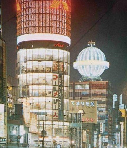 【37】高度経済成長期に始まった歩行者天国。1964年(昭和39年)東京オリンピックが開催され、1969年(昭和44年)GNP世界第2位となるなど、高度経済成長の時代に。1965年(昭和38年)完成した三愛ドリームセンタービル。リコー創業者市村清が戦後間もない1946年(昭和21年)旧六十九銀行跡地に2階建のビルを建設し、以後この地から経営拡大。法隆寺五重塔をヒントに「建物中心に大きな柱を立ててビル全体を総ガラス化させた円筒型のビル」を考案、名称も一般公募で決定した。外壁には社章である眼鏡のマークが配してあった。三菱電機スカイリングのネオンも長年親しまれた。その他にも、銀座最大を誇った東芝ビル、銀座ライオンビル、名鉄メルサ、資生堂ザ・ギンザなど、新しいビルが次々と建てられた。中央通りでは、1970年(昭和45年)歩行者天国が実施されるようになり休日の定番となる。【37】1965年(昭和38年)頃・三愛ビルネオン