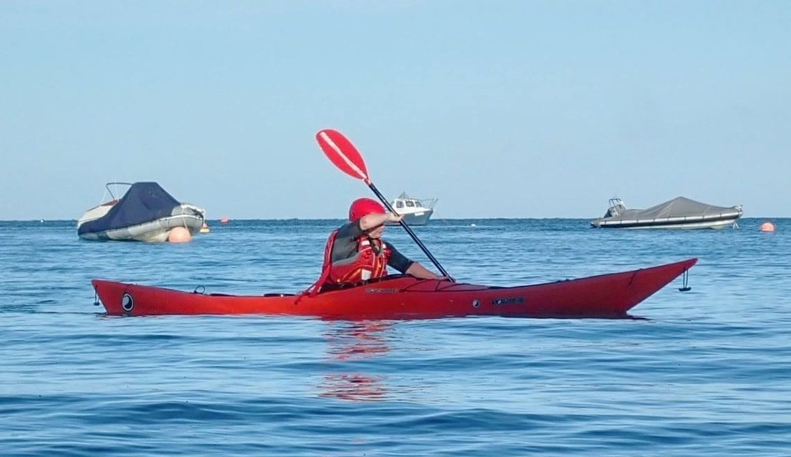 Photo of Sea Kayaker coached through Bow under as part of a training session.