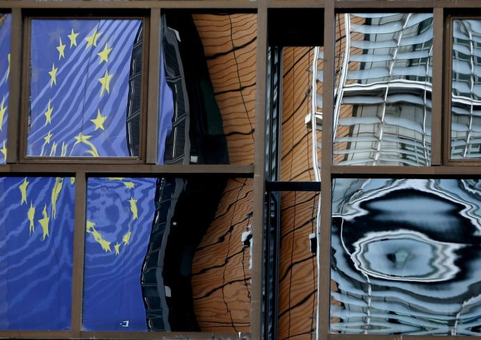 The facade of the European Commission headquarters is reflected in the windows of the EU Council building in Brussels.REUTERS