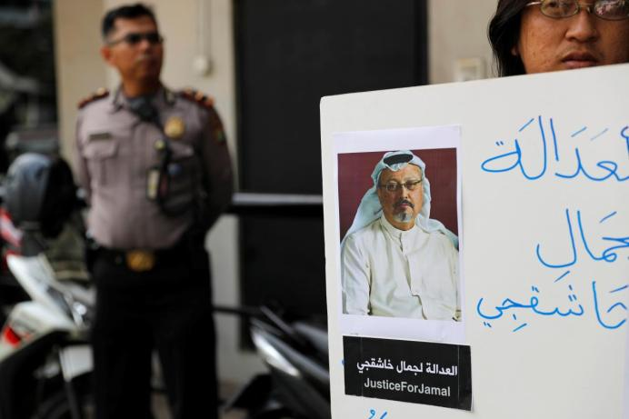 A policeman stands guard as an Indonesian journalist holds a placard during a protest over the disappearance of Saudi journalist Jamal Khashoggi in front of the Saudi Arabia embassy in Jakarta, Indonesia, October 19, 2018. REUTERS/Beawiharta