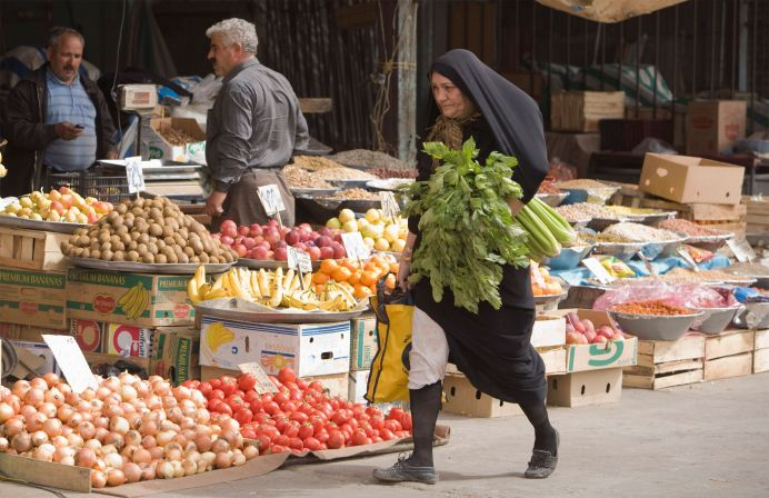 A woman walks with her day's shopping at a vegetable market in Islamshahr, 50km (31 miles) southwest of Tehran. REUTERS