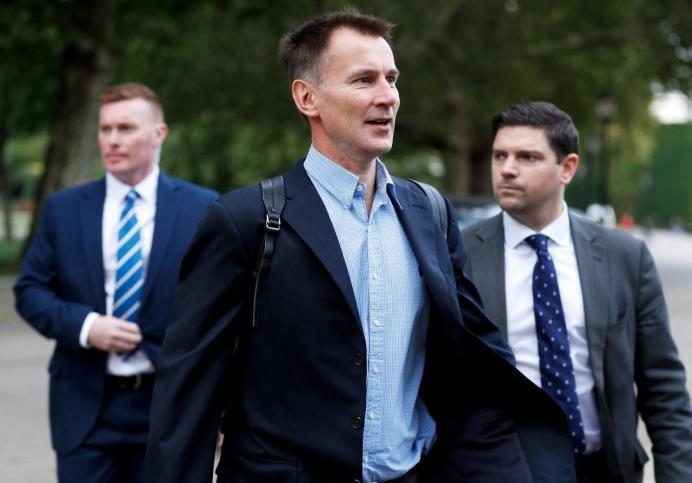 FILE PHOTO: Britain's Foreign Secretary Jeremy Hunt walks towards the Foreign Office in London. REUTERS