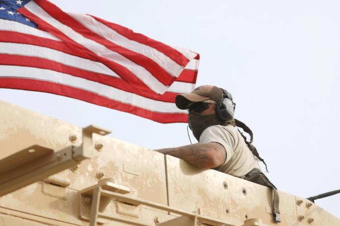 FILE PHOTO: A member of U.S forces rides on a military vehicle in the town of Darbasiya next to the Turkish border. REUTERS/Rodi Said