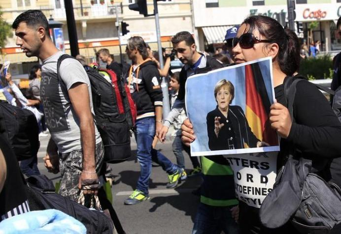 A woman holds a picture of German Chancellor Angela Merkel as migrants set off on foot for the border with Austria from Budapest, Hungary, September 4, 2015. REUTERS