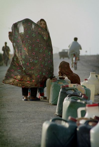 FILE PHOTO: Young Iranian women wait with their jugs of water at the roadside for transportation to their village at a water distribution point outside Zabol in south eastern Iran. REUTERS./