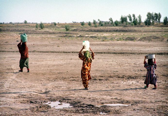 FILE PHOTO: Young Iranian women carry jugs of water, filled at water distribution point, to their village outside Zabol in south eastern Iran. REUTERS./