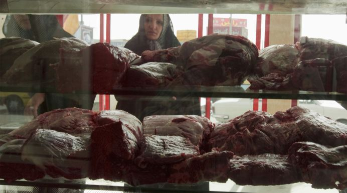 FILE PHOTO: A woman looks at meat displayed in a butcher's shop in Islamshahr, 50km (31 miles) southwest of Tehran, Iran.