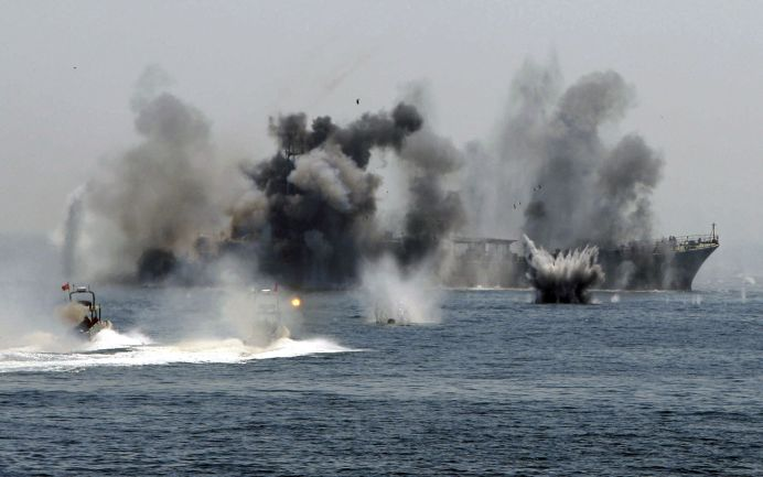 An Iranian warship and speed boats take part in a naval war game in the Persian Gulf and the Strait of Hormuz in this file photo from Reuters.
