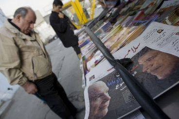 FILE PHOTO: Iranians look at newspapers with pictures of U.S. President-elect Senator Barak Obama (D-IL) (R) and former U.S. Republican presidential nominee Senator John McCain (R-AZ) at a news stand in Tehran November 5, 2008. REUTERS/Morteza Nikoubazl