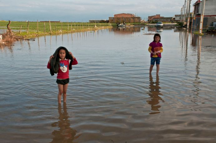 Children stand in a flooded street in Mazandaran province, Iran, March 22, 2019. Picture taken March 22, 2019. Reuters