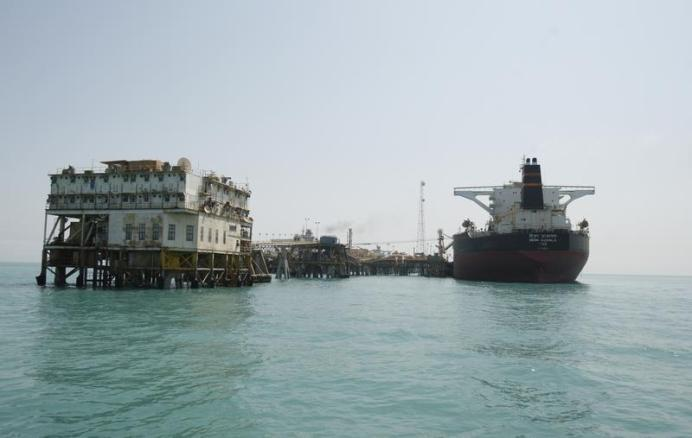 FILE PHOTO: A crane and vessels are seen at the Al-Basra terminal in southern Iraq. Reuters