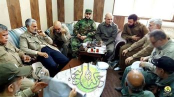 In the centre wearing camouflage, Akram Kaabi, the leader of Nujaba, at a meeting in Falluja, Iraq. To his right, with a beard, sits Qassem Soleimani, the head of the Iranian Revolutionary Guards' Quds Force. The Nujaba dedicated a song to Soleimani. REUTERS