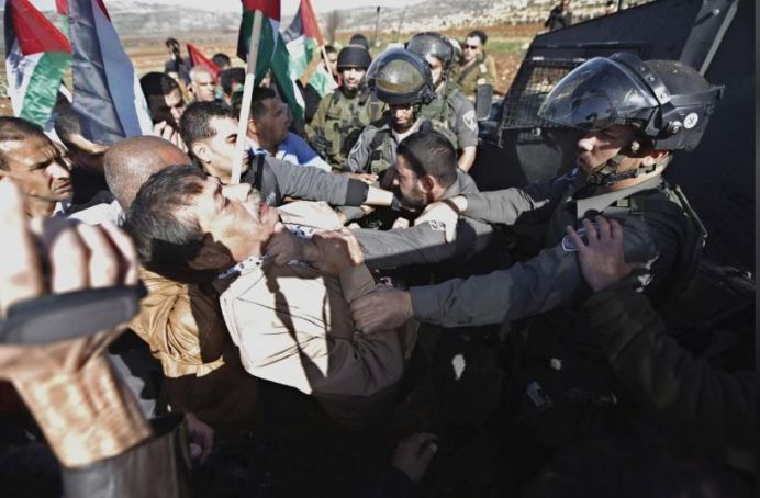 FILE PHOTO: Palestinian minister Ziad Abu Ein (L) scuffles with an Israeli border policeman near the West Bank city of Ramallah December 10, 2014. REUTERS/Mohamad Torokman