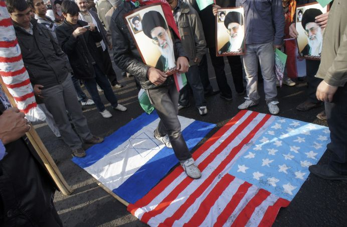 FILE PHOTO: A man holds a picture of Iran's Supreme Leader Ayatollah Ali Khamenei while walking on representations of the U.S. and Israeli flags during a demonstration. REUTERS