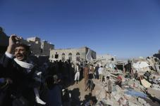 FILE PHOTO: People gather near houses destroyed by an overnight Saudi-led air strike on a residential area in Yemen's capital Sanaa. Reuters