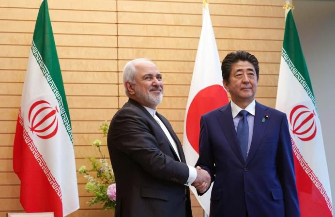 FILE PHOTO: Iranian Foreign Minister Mohammad Javad Zarif, left, and Japanese Prime Minister Shinzo Abe, right, shake hands at Abe's official residence in Tokyo Thursday, May 16, 2019. Eugene Hoshiko/Pool via REUTERS