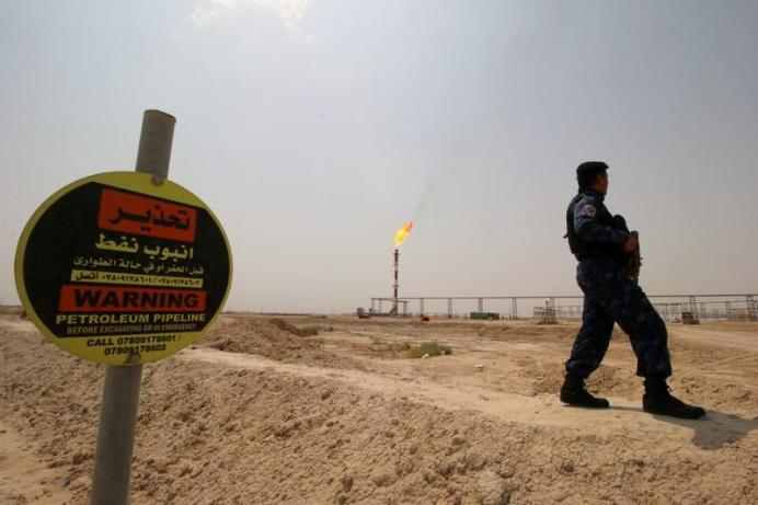 FILE PHOTO: A member of the oil police force guards the entrance of the West Qurna-1 oil field, which is operated by Exxon Mobil, near Basra, Iraq, May 20, 2019. REUTERS/Essam Al-Sudani/