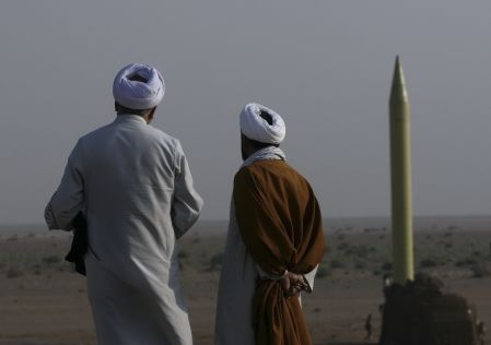 FILE PHOTO: Two Iranian clerics stand near a surface to surface missile which is ready to be launched during a war game near the city of Qom, about 120 km (75 miles) south of Tehran. REUTERS